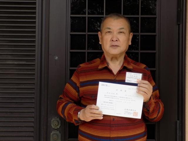 自宅玄関前にて。届いた献体登録証とカードです